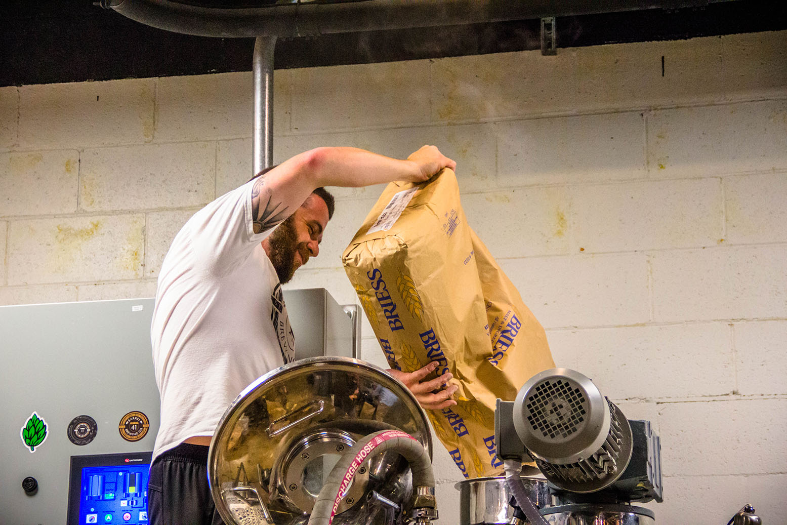 Nathan Sharpless pouring barley into a brewing drum